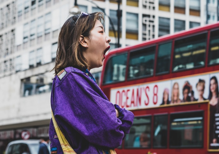 You should not fall asleep if you have a concussion US girl on purple yawning on a busy streets - 4 Myths About Modern Medicine