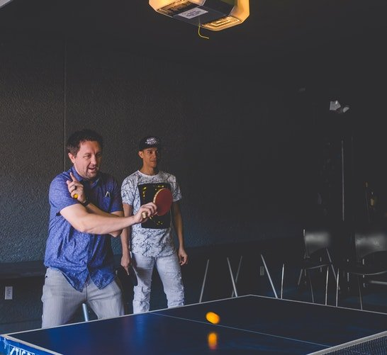 It give You More Energy US man in blue playing table tennis with another man as his audience - 4 Reasons Why Sports Make Us Happier